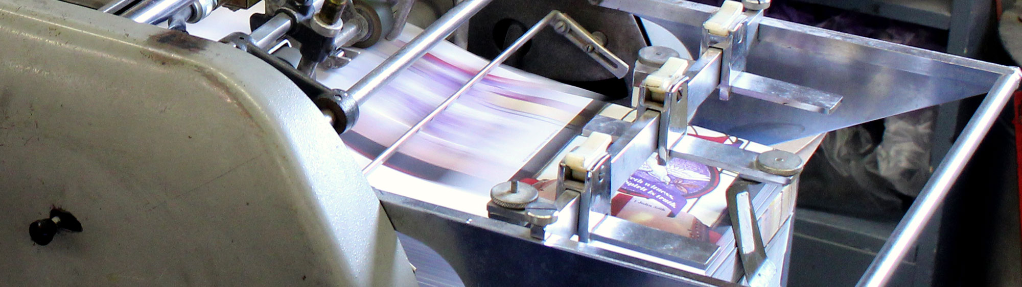 Weekly Church bulletins being printed in a commerical printer at Cathedral Press in Long Prairie, MN